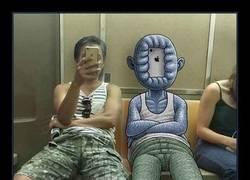 Enlace a Artista dibuja monstruos al lado de extraños en el metro