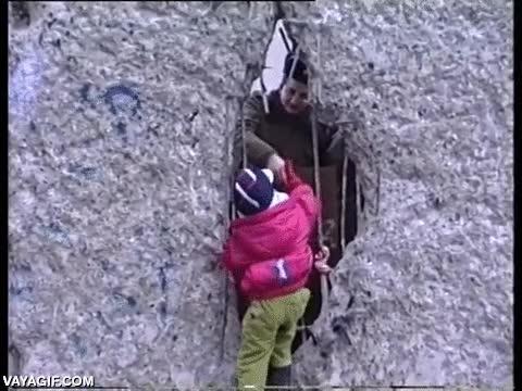 Enlace a Un niño dando la mano a un guardia de Alemania del Este a través del Muro de Berlín en 1989