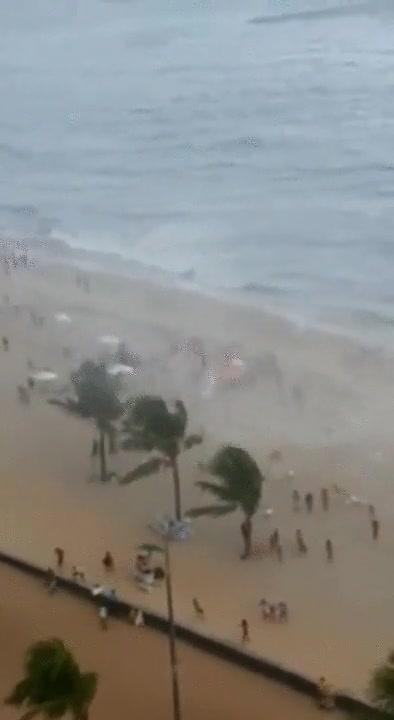 Enlace a Un pequeño tornado entra desde el mar a la playa y se lleva a varias personas por delante