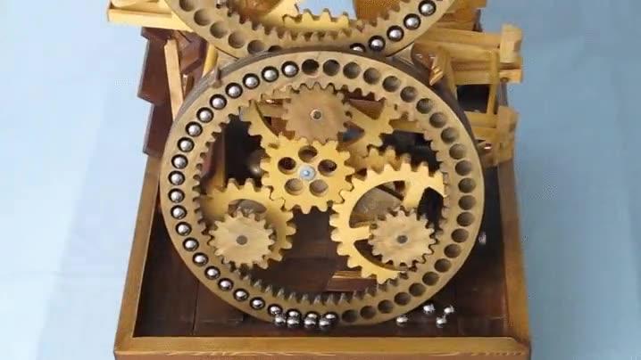 Enlace a Un mecanismo de madera transportador de bolas metálicas