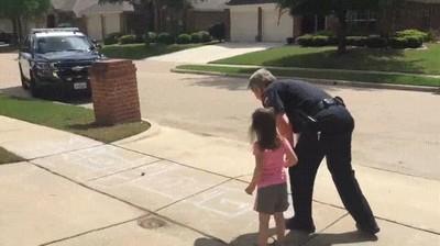 Enlace a Policía tomándose su tiempo libre para jugar con una niña