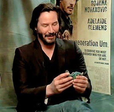 Enlace a Keanu Reeves jugando con una figura de su meme con cara triste