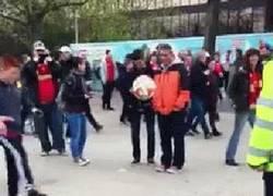 Enlace a GIF: Una mujer policía jugando al balón con tres niños en los alrededores de Wembley