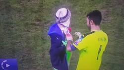 Enlace a Buffon le firma una camiseta a un chico que salta al campo mientras se juega el partido