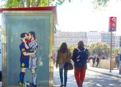 Enlace a Un graffitero ha pintado el sueño húmedo de culés y merengues: el morreo de Messi y Cristiano
