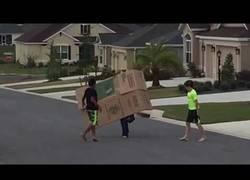 Enlace a Tres chavales intentando mover una caja de cartón