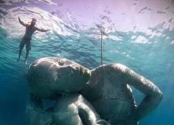 Enlace a Inmensa estatua submarina de una mujer sosteniendo el océano sobre sus hombros