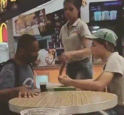 Enlace a Empleada de un restaurante de comida rápida ayudando a alguien que realmente lo necesita