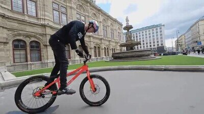 Enlace a Tremendo truco con un skate sobre la bici