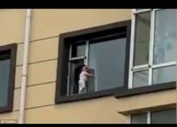 Enlace a Graban como un niño pequeño se da un paseo mañanero por una ventana de un quinto piso