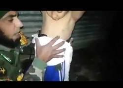Enlace a Graban como un soldado iraquí le quita un cinturón de explosivos colocado por ISIS a un niño