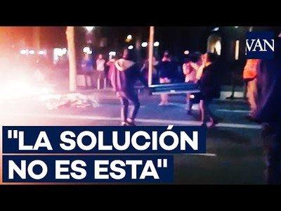 Una señora evita con argumentos que un manifestante siga quemando mobiliario urbano