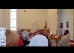 Enlace a Un sacerdote de la Iglesia ortodoxa rusa bendice a su feligreses con una manguera