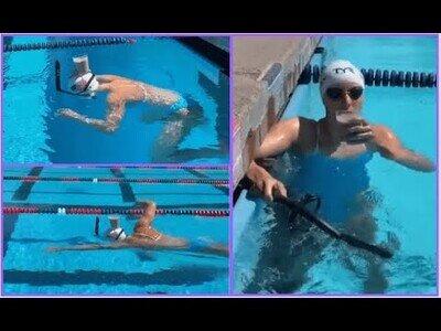 La nadadora Katie Ledecky cruza una piscina con un vaso con leche en la cabeza