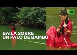 Enlace a Bailando sobre una caña de bambú en un río