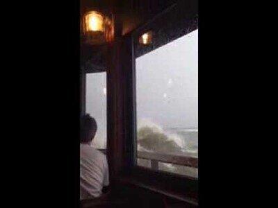 Una fuerte ola rompe con los cristales de un restaurante